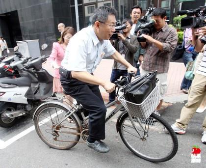 Ke Wen-je poses on a bicycle