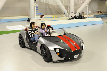 A mother and child driving on an indoor track at Mega Web in Tokyo