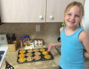 daughter helping creating mini peach and apple pies