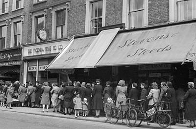 D24990 Women and children queue for fruit and vegetables from a London greengrocer, 1945. Fruit and vegetables were not rationed in Britain during the Second World War, but some, like bananas, oranges and onions, were either unobtainable or in short supply. © Imperial War Museum