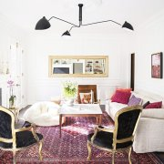 Bold living room with a red and magenta palette, grounded by black and gold fauteuils.