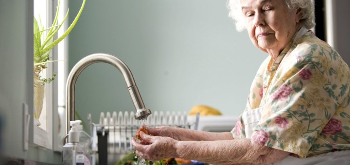 Old woman in kitchen pictured while washing carrots and radishes