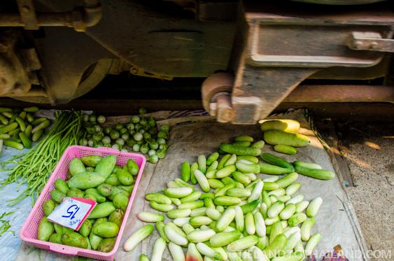 The train passes just above the produce at the Maeklong Railway Market
