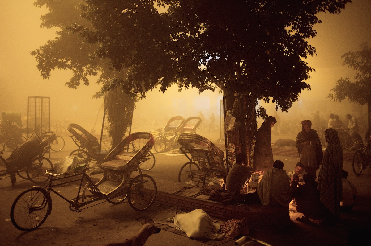 Rickshaw riders gather around a fire beneath streetlighting in the dawn chill of Moradabad railway station.  Moradabad, Uttar Pradesh, India. November 2006