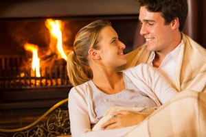 couple sitting in room warmed by fireplace and clean HVAC air ducts
