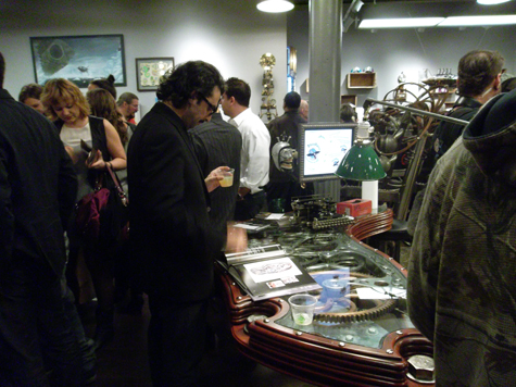 A gentleman checks out the artist catalog that sits on the Steampunk Executive Gear Desk, created by Dale Mathis
