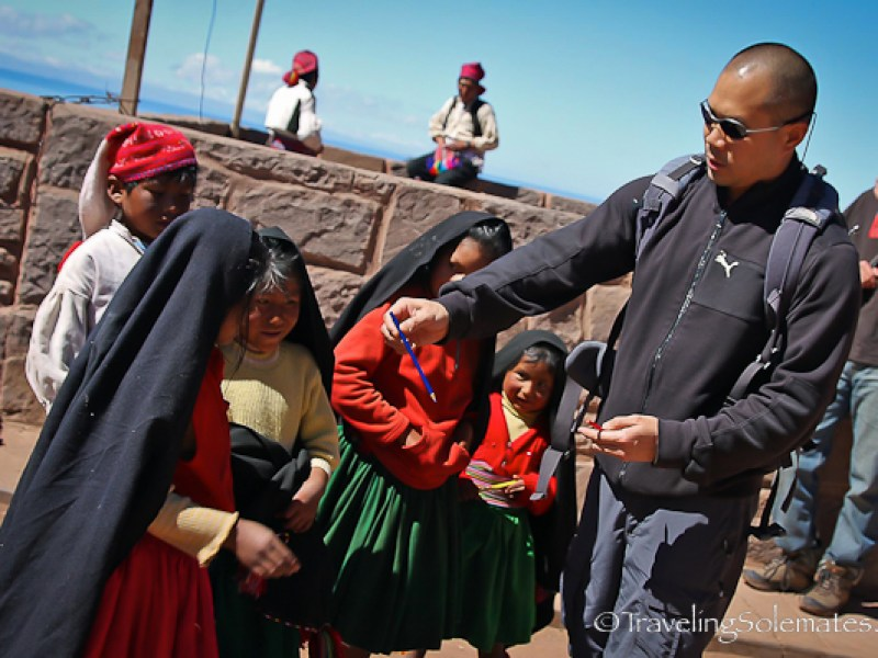 Giviing out pencils to children on Taquile Island, Lake Titicaca, Peru