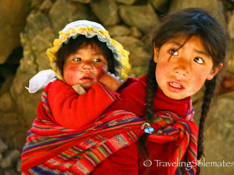 Little girl carrying baby in Pitacancha, Lares Valley Trek Peru
