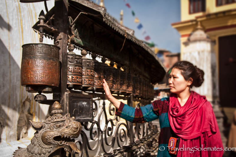 A woman spinning a series of prayer wheels in Swayambhunath Temple, Kathmandu, Nepal