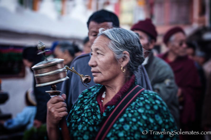 A woman spinnin a prayer wheel while circumambulating a stupa in Bodnath, Nepal
