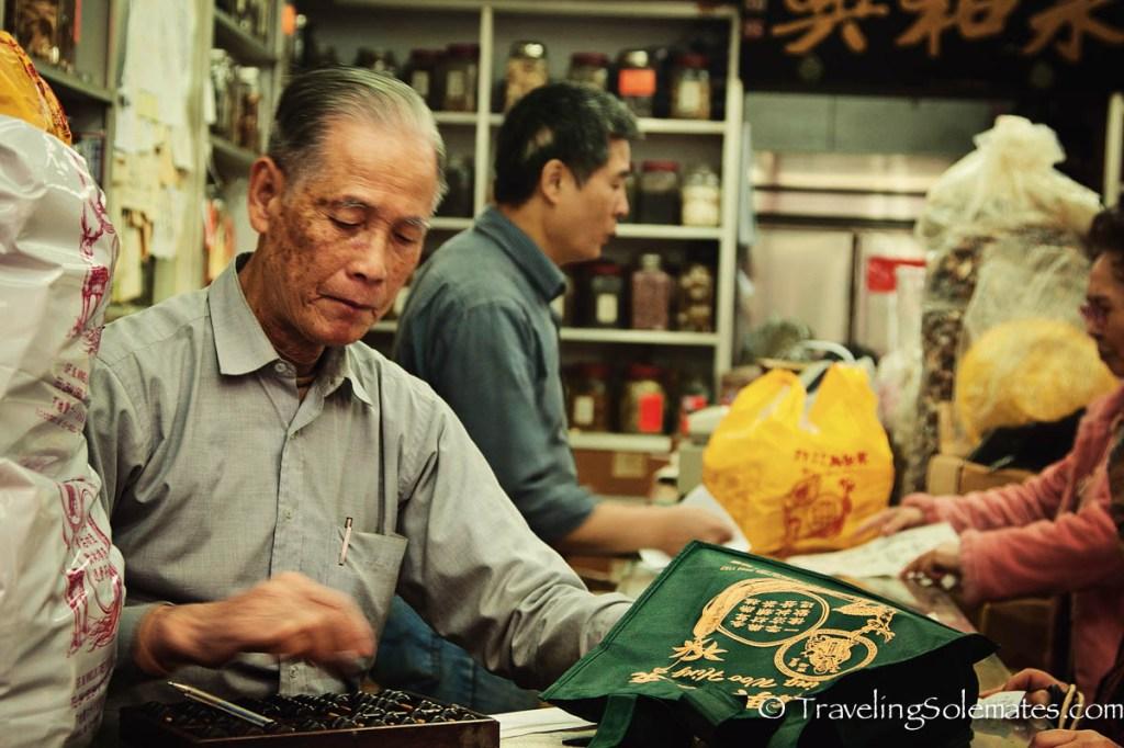 Vendor using abacus in Medicinal Shop in Hong Kong