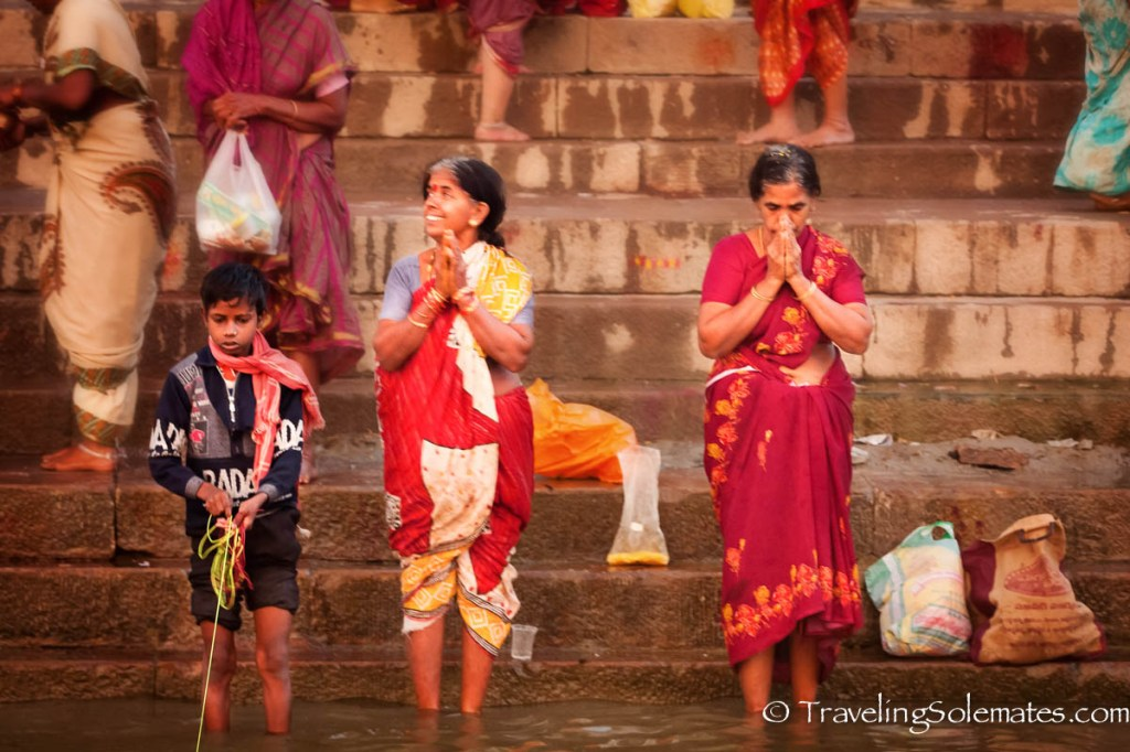 A boy fishing and women praying in Ganges River, Varanasi India