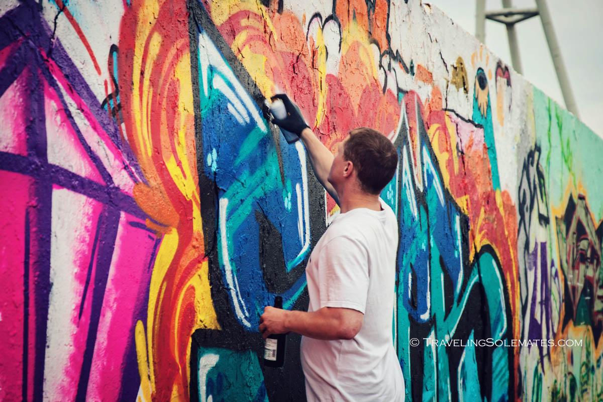 A man spray painting on Berlin Wall in Mauerpark, Berlin, Germany