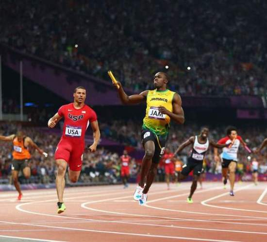 LONDON, ENGLAND - AUGUST 11:  Usain Bolt of Jamaica celebates as he crosss the finish line ahead of Ryan Bailey of the United States to win gold and set a new world record of 36.84 during the Men's 4 x 100m Relay Final on Day 15 of the London 2012 Olympic Games at Olympic Stadium on August 11, 2012 in London, England.  (Photo by Michael Steele/Getty Images)