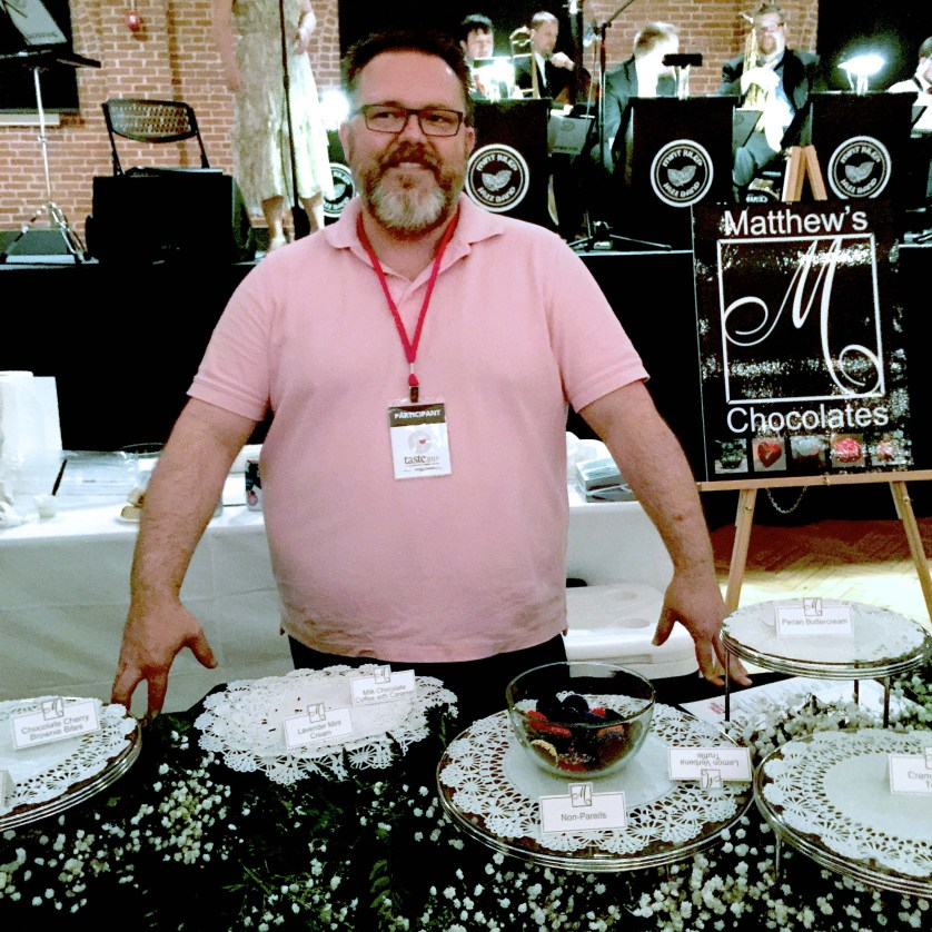 Matthew Shepherd of Matthew's Chocolates of Hillsborough, NC stands before his depleted table of decadent chocolates (use your imagination here).