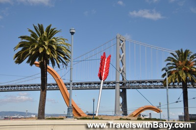 View of the bow and arrow (Cupid) sculpture beside the San Francisco Bay Bridge