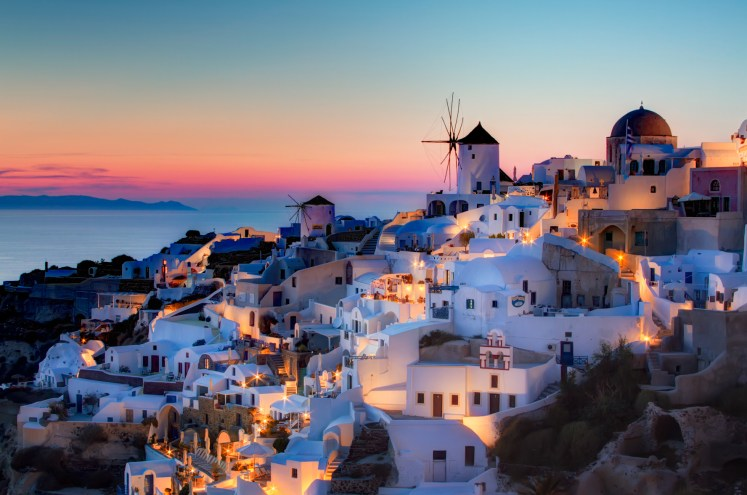 Sunset in Oia, Santorini. Here is my version of the sunset shot in Oia. This is a blend of 3 shots, 1.3 to 20 seconds, processed as follows: 1) Reduce noice on all 3 raws. 2) Create HRD in Photomatix 3) Blend using Exposure Fusion, sliders set to produce the most natural looking image while still showing some detail in the very dark areas. 4) PS smart sharpen. 5) PS burn the bottom 6) Nik Brilliance and warming 7) Nik Indian summer to warm th elights, masked to not affect the rest. 8) Nik sunlight, brushed over the buildings to add more light 9) Nik Glamour Glow to remove detail in the dark areas. 10) Detailed curves lightening pn windmills. 11) Dodge buildings that were too dark.
