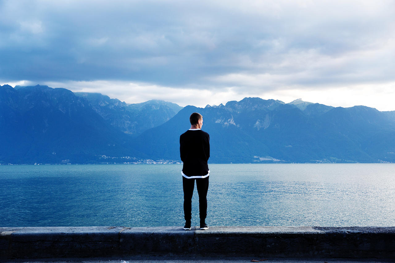 Man standing on the edge of the sea looking at the mountains