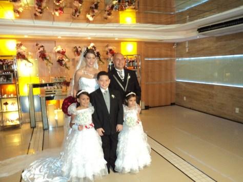 Foto dos noivos Valéria e Anderson com daminhas e pajem do casamento