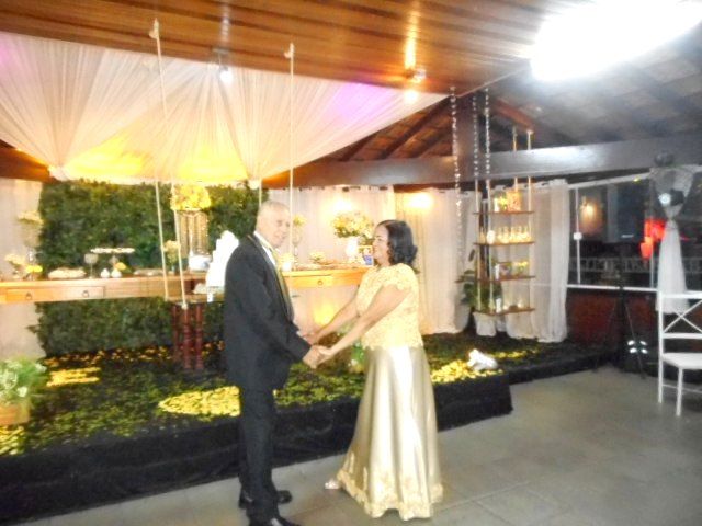Foto do casal Eurico e Josilda em frente a mesa de bolo e doces.