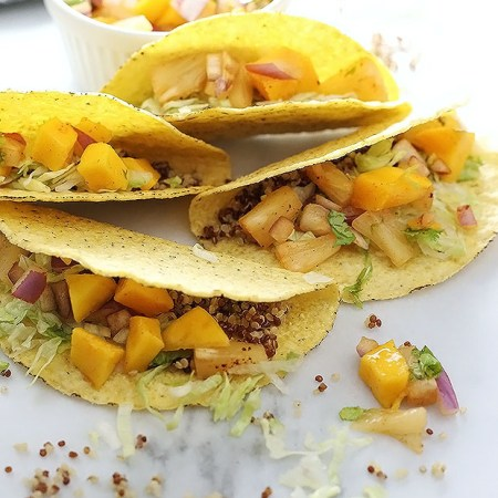 Vegan Caribbean Quinoa Tacos! Nutty quinoa meets fresh and spicy chili pineapple mango salsa in these tacos! These tacos are super quick and easy to make. Vegan and Gluten Free! / TwoRaspberries.com