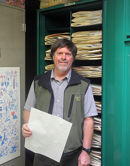 Jim André, director of the NRS's Sweeney Granite Mountains Desert Research Center, holds a specimen in front of a cabinet of his reserve herbarium. His 7,000 California specimens will bring the CCH to over 2 million specimen records. Image courtesy Jim André