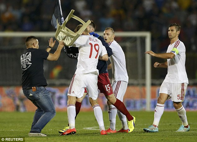 A Serbia's fan attacks an Albanian footballer with a chair, during the Serbia - Albania football match on 14 October 2014.
