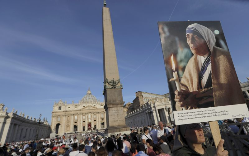A nun holds a photo of Mother Teresa before the start of the canonisation Mass in St Peter's Square (AP)