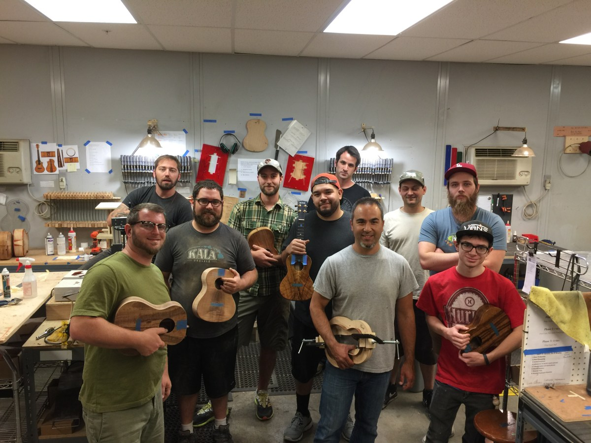 The Kala Elite team shows off some of some of the ukes its working on, with Jason Villa in the gray shirt.