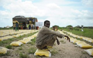 Photo: A man rests on a bag of rice distributed by Qatar Charity for iternally displaced people (IDPs) affected by flooding and clan conflict in Jowhar, Somalia.
