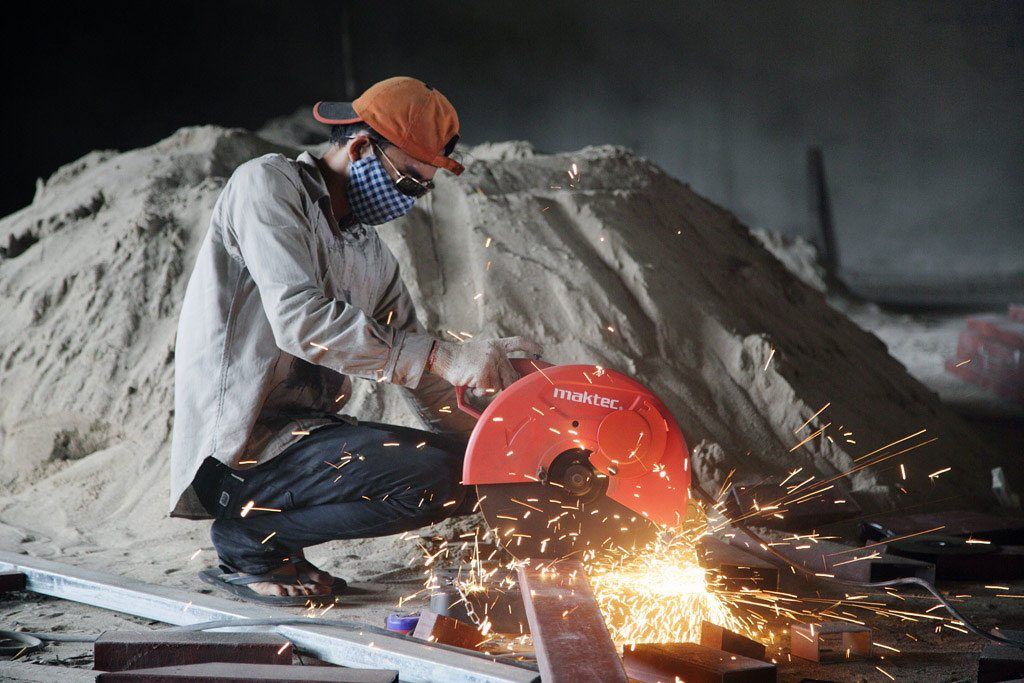 A construction worker cuts through a steel beam at a construction site in Luang Prabang, northern Lao People's Democratic Republic. Photo: ILO/Adri Berger