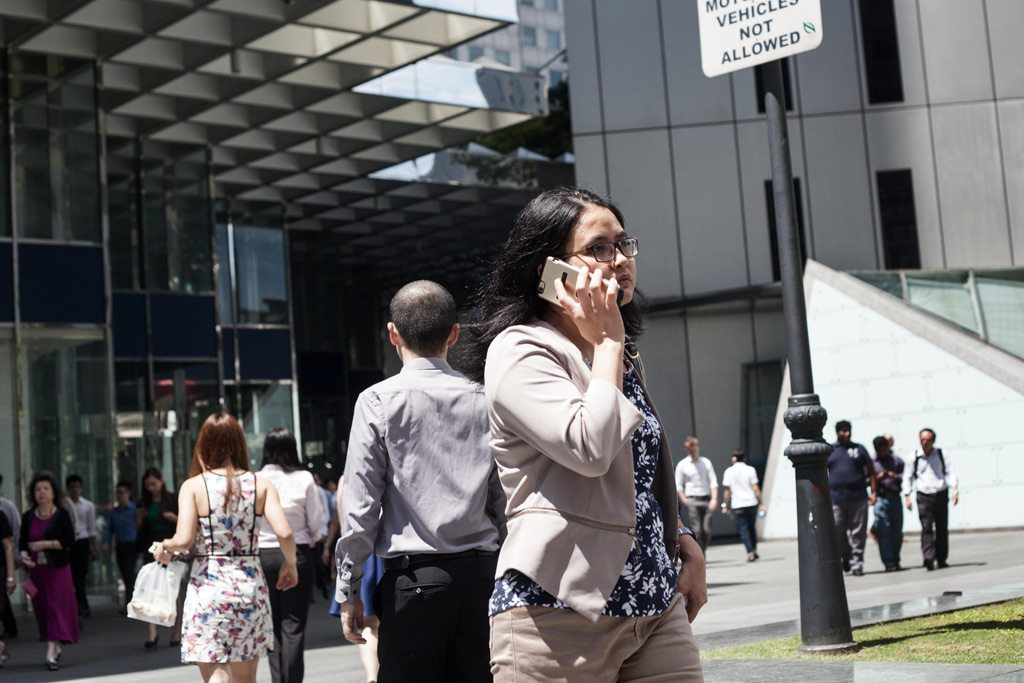 A woman walks speaks on the phone as she walks to work in Singapore. Photo: ILO/Giorgio Taraschi