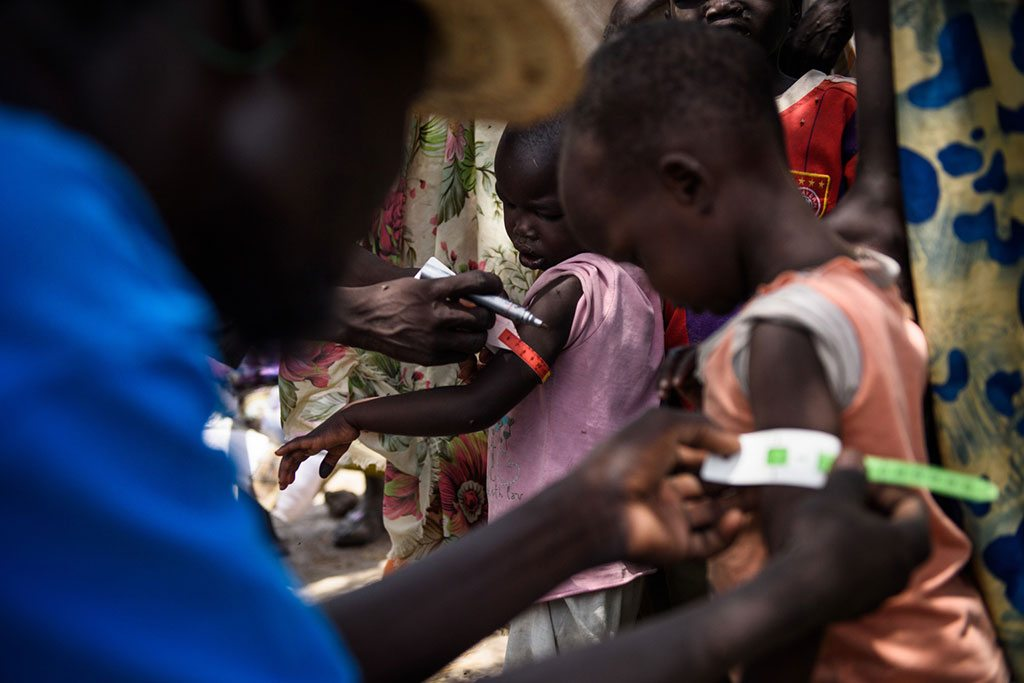 A UNICEF nutrition volunteer measures the mid-upper arm circumference (MUAC) of a child during a health screening as part of a UNICEF Rapid Response Mission to the village of Aburoc, South Sudan. Photo: UNICEF/Hatcher-Moore