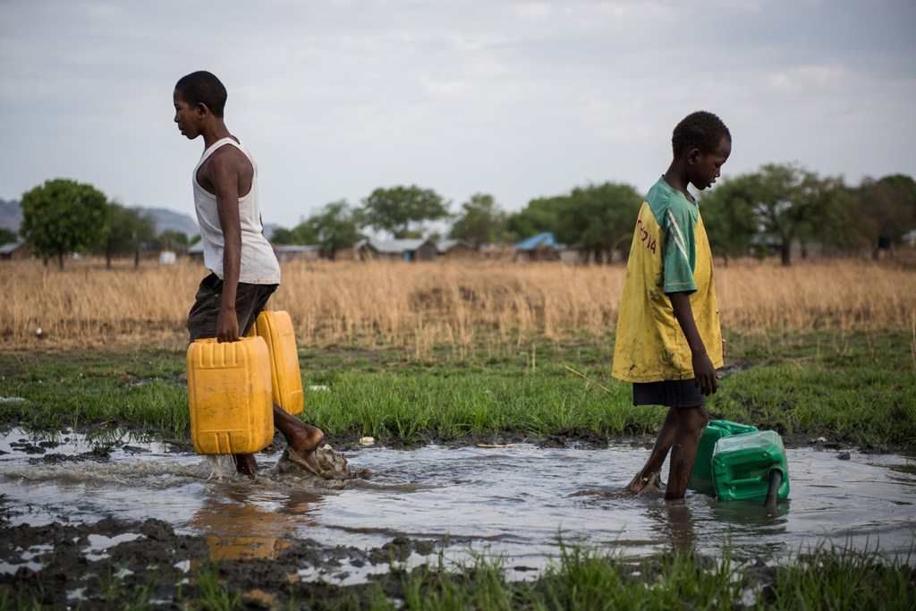 Two boys, one 16 years old and the other 12, collect water from a damaged pipe on the outskirts of Juba, South Sudan. The water is pumped from the White Nile River, but is untreated, risking the health of those who consume it. Photo: UNICEF/Hatcher-Moore