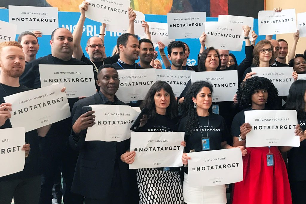 Staff stand together at United Nations Headquarters in New York to draw attention that civilians are #NotATarget. Photo: UN News/Paulina Carvajal