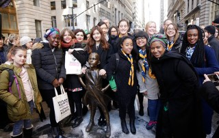 L-R: Unami Moatswi; Daniela Zelaya; Ashken Aslikyan; Joyce Lee Boram and Heejin Lim (World YWCA); Candela Gonzalez; Zoelisoa Rakotomanana; Danae Fredes-Toledo; Emma Guthrie; Anna Spencer and Jean-Ann Ndow (WAGGGS); with UN Women Executive Director Phumzile Mlambo-Ngcuka at the Fearless Girl statue on Wall Street. Photo: UN Women/Ryan Brown