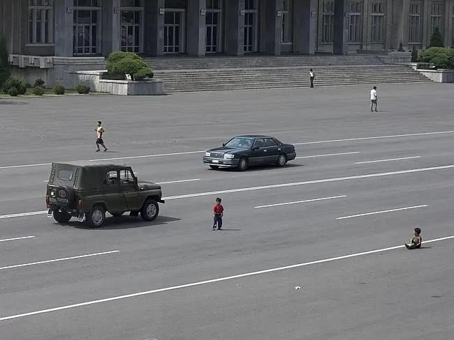 """""""A medida que los coches se van generalizando en Pyongyang, los campesinos se van acostumbrando a verlos. Los niños juegan en medio de las avenidas principales como antes, cuando no había coches a la vista"""" Eric Lafforgue."""
