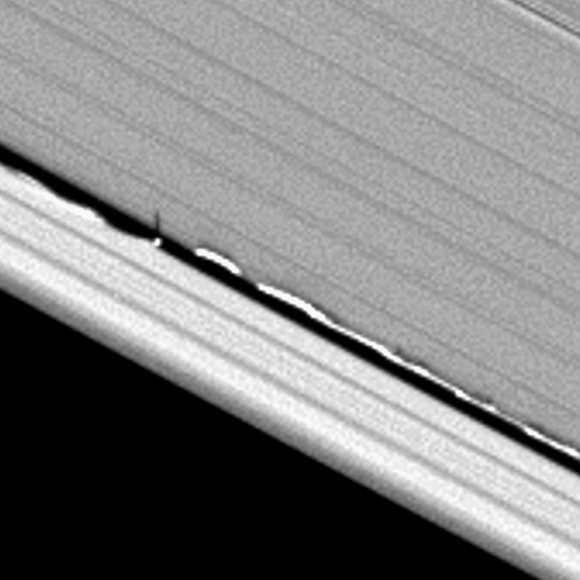 Looming vertical structures, seen here for the first time and created by Saturn's moon Daphnis, rise above the planet's otherwise flat, thin disk of rings to cast long shadows in this Cassini image.  Credit: CICLOPS