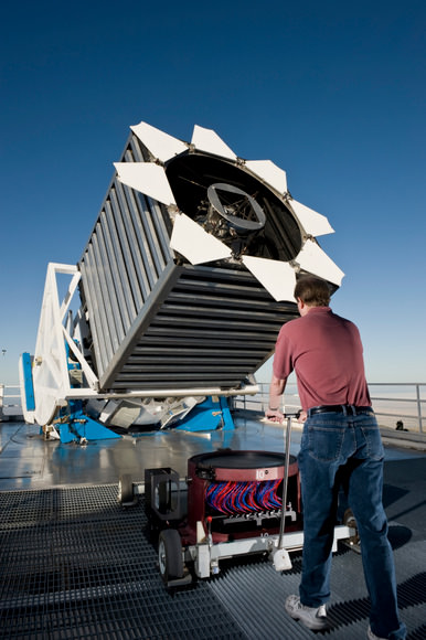 "Senior Operations Engineer Dan Long loads the first cartridge of the night into the Sloan Digital Sky Survey telescope. The cartridge holds a ""plug-plate"" at the top which then holds a thousand optical fibers shown in red and blue. These cartridges are locked into the base of the telescope and are changed many times during a night. Phot"