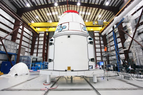 SpaceX, Dragon spacecraft stands inside a processing hangar at Cape Canaveral Air Force Station in Florida. Teams had just installed the spacecraft's solar array fairings. Credit: NASA/Kim Shiflett
