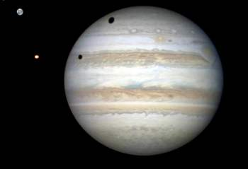 A rare double transit of Jupiter's moon Ganymede (top) and Io on Jan. 3, 2013. Here, the sun is shining from the left causing shadows cast by the moons to fall onto the planet's cloud tops. Credit: Damian Peach