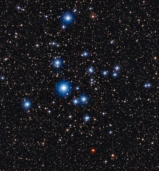 This image from the Wide Field Imager on the MPG/ESO 2.2-metre telescope at ESO's La Silla Observatory in Chile, shows the bright open star cluster NGC 2547. Between the bright stars, far away in the background of the image, many remote galaxies can be seen, some with clearly spiral shapes. Credit: ESO