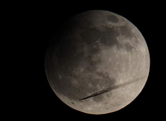 Airliner flies through partial eclipse! On April 25, 2013, around 10:10 PM local time, the partial Lunar eclipse was at its maximum. The Moon only traveled 1,3% into the central Earth shadow (umbra). The event was visible from Europe, Asia and Australia. Canon EOS 600D on 130 mm (f/7,1) triplet Apo-refractor settings: 1/200 exposure at ISO 100.  Credit and copy