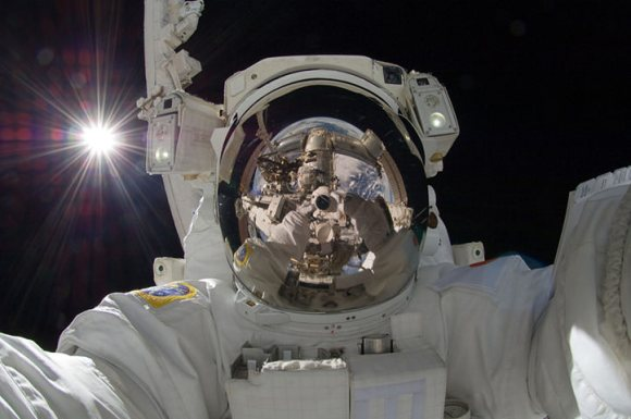 "JAXA astronaut Aki Hoshide takes a self-portrait during Expedition 32 in September 2012. ""Visible in this outworldly assemblage is the Sun, the Earth, two portions of a robotic arm, an astronaut's spacesuit, the deep darkness of space, and the unusual camera taking the picture,"" NASA wrote. Credit: NASA"