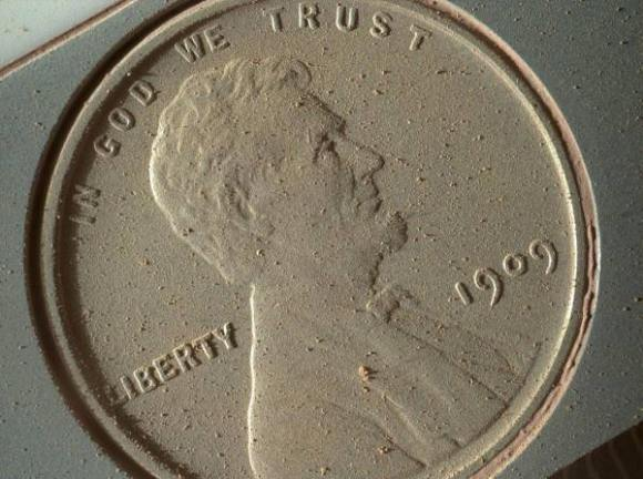 A 1909 penny being carried by the Mars Curiosity rover is caked with dust on Oct. 2, 2013, after 14 months on Mars. Credit: NASA/JPL-Caltech/MSSS/Planetary Science Institute