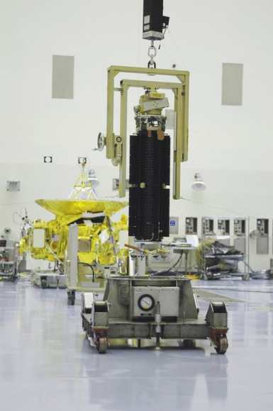 The plutonium-fueled RTG (foreground) awaiting installation on New Horizons (background). (Credit: NASA).