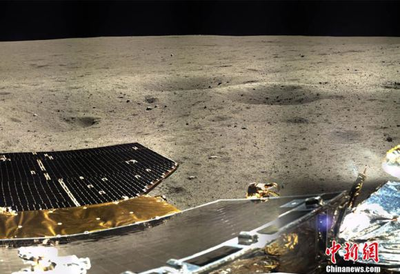 The lander's solar panels stand out in the foreground with a smattering of small craters nearby. Credit: Chinanews.com