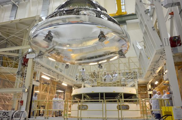 The Orion crew module for Exploration Flight Test-1 is shown in the Final Assembly and System Testing (FAST) Cell, positioned over the service module just prior to mating the two sections together. Credit:   NASA/Rad Sinyak
