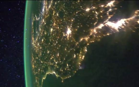 Photo taken of Earth at night from the International Space Station showing bright splashes of city lights and the airglow layer off in the distance rimming the Earth's circumference. Credit: NASA