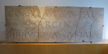 """Placa romana que muestra """"Colonia Iulia Augusta Faventia Paterna Barcino"""" en el MUHBA"""